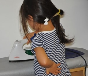 """This girl has listened to the teacher, who just reminded her go put her """"other hand"""" behind her back while ironing."""