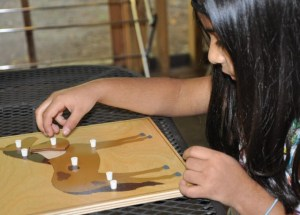This girl is practicing the names of the parts of a horse while repeatedly removing and replacing them into a puzzle frame.