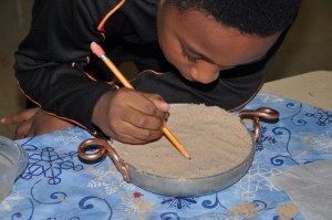 Recently we made candles.  First, we packed a pot with sand.  Then, we drew a design for the perimeter of the candle.