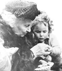 Dr. Maria Montessori looking at something with a child and talking with her.