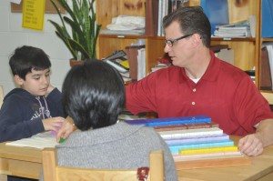 After presenting, a child allows his father to have a go at cubing with the material at Open House.