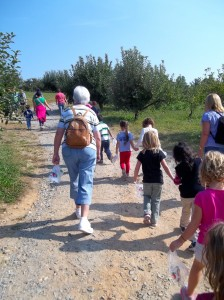 The goal of all the Sensorial Material at the Primary is connecting the child to nature.  Here some older Primary children head down a path leading to an apple orchard full of ripe fruit.