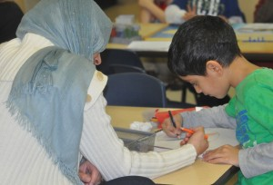 A parent's patience in participating with a child at the Parent/Child Open House.