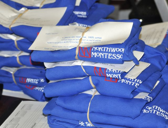 """Here, Northwoods t-shirts are ready to be distributed for the Fall Carnival and """"Spirit Day."""" We find that our former students love their Northwoods shirts and wear them thin. In the office, we often see how many we can wear on Fridays."""