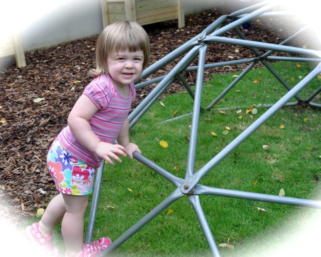 Toddler Community Geodome climbing out in front of the building.