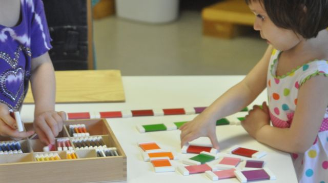 Two children work together to match color tablets and recall their names.