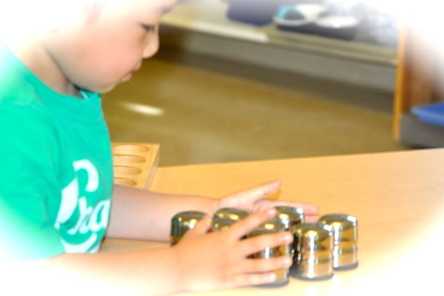 A child savors the sight of his his Smelling Bottles, containers with tiny holes in their tops, releasing  different, very subtle scents to match.