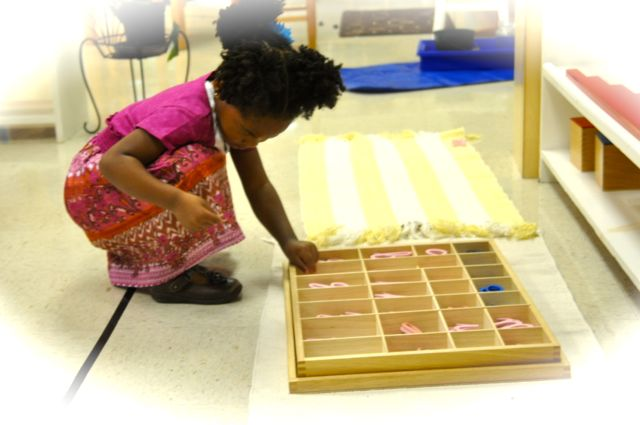 Here's a girl who has carried two mats and a Moveable Alphabet to a space on the floor.  She's looking for the first sound of the first word in her story.