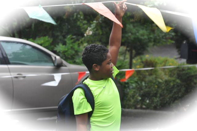 A child sees someone encumbered with bags and offers to lift an obstacle---a thoughtful gesture.