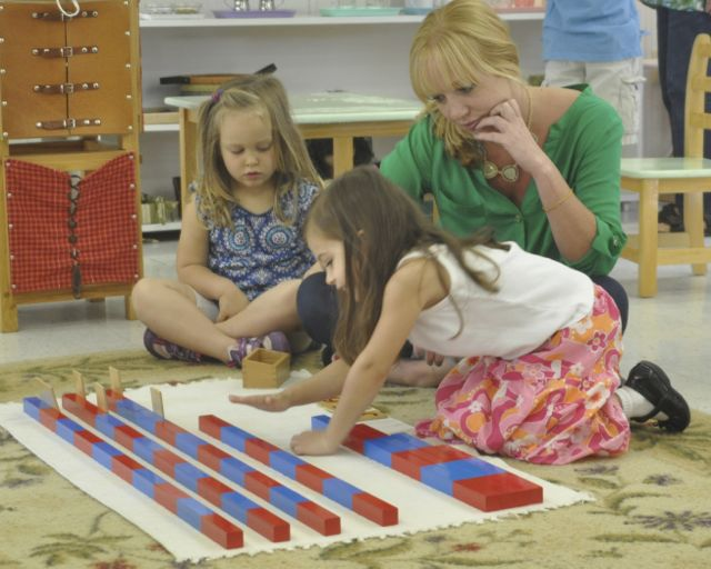 A teacher guides a child as she aligns wooden numeral cards to her arranged Number Rods. Another child looks on, absorbing images of this process.