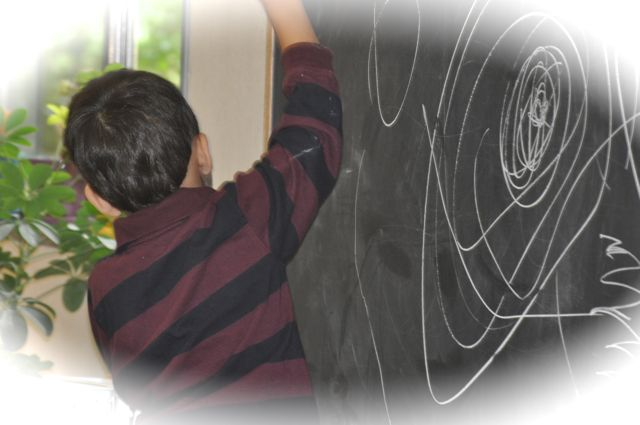 Just experimenting with chalk on the large chalkboard, we can use our entire arm to create lines, up and down, around, and in all directions.