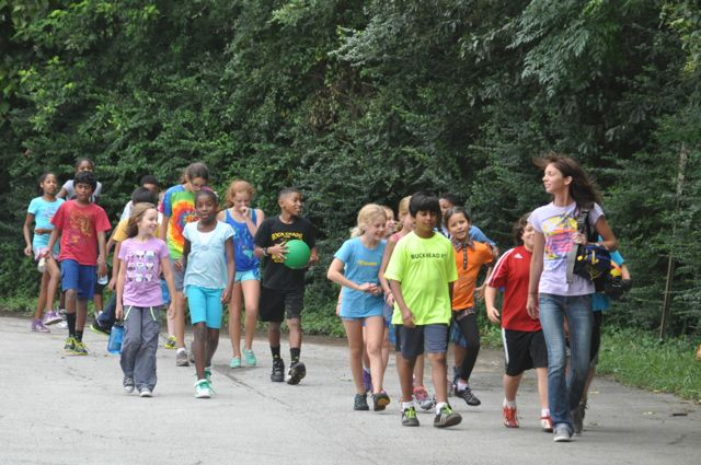 A group of children walk together, as a group, to the field to play as the Assistant supervises.