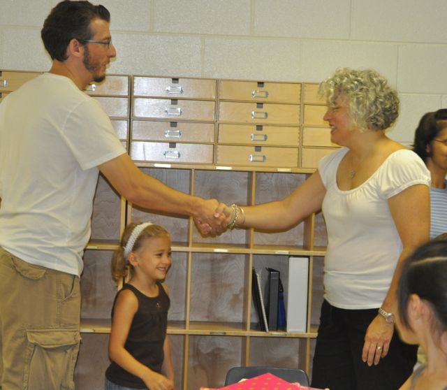 A parent and a teacher greet each other at Elementary Open House on Friday before the first day of class.