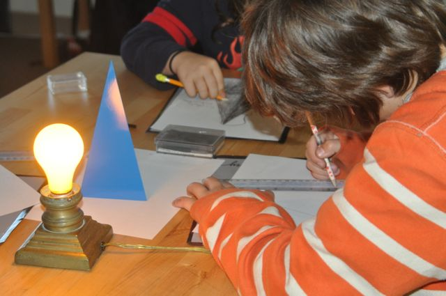 Elementary children capturing the shape of a geometric figure, the triangular prism, and its shadows, employ the motor control and self-discipline they developed in Primary to help them discover geometric relationships while they hone their sketching and shading skills.