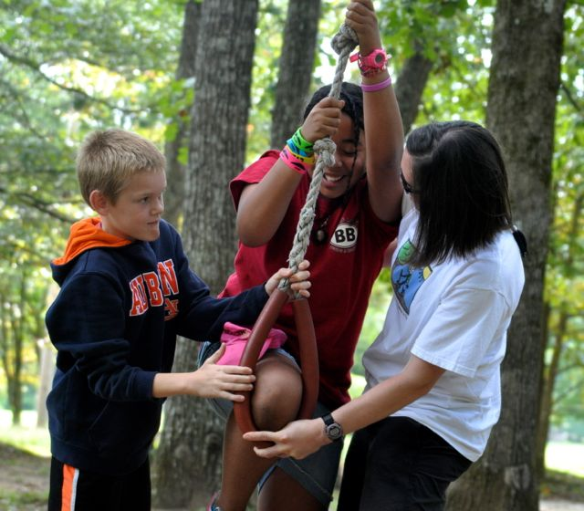 """Supportive friends help get a child in position for a swing across the """"Lake of Fire"""" at Nature's Classroom."""